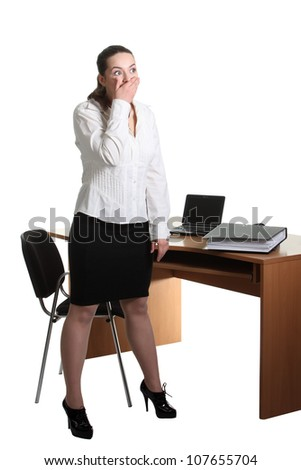 Shocked businesswoman stay near her office table and close mouth by hand - stock photo