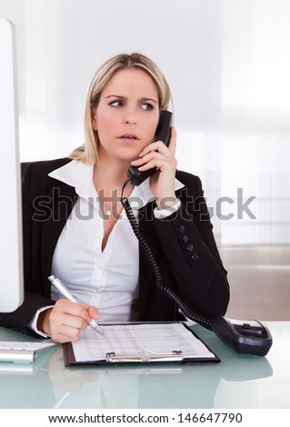 Shocked businesswoman talking on telephone and holding pen - stock photo