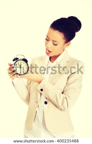 Shocked businesswoman with alarm clock. - stock photo
