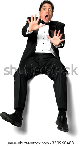 Shocked Caucasian man with short black hair in a tuxedo sitting with person - Isolated - stock photo