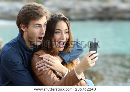 Shocked couple watching a smart phone on holidays on the beach - stock photo