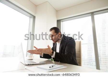 Shocked entrepreneur looking with surprise, pointing at computer on desk. Businessman upset because of unexpected data loss, wrong work result, bad job done, software error, nonsense on laptop screen