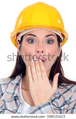Shocked female builder covering mouth