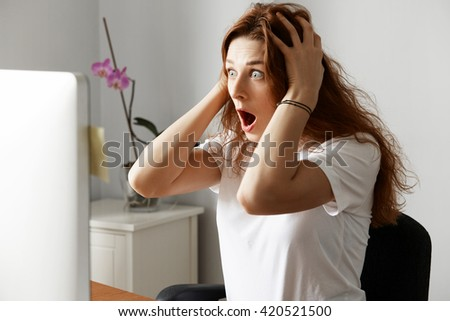 Shocked female office worker having unsaved data problem on laptop while working in the office. Young woman freelancer looking in horror at the computer screen with hands on head and wide open mouth - stock photo