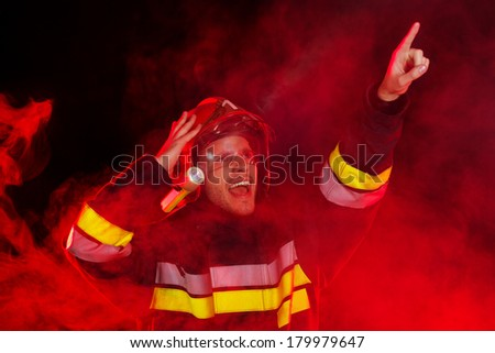 Shocked firefighter in action. Shouting fireman in smoke holding hand on helmet and pointing up. Head and shoulders studio shot on black background.
