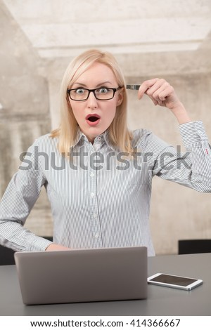 Shocked freelance lady holding flash card near her head showing about bad memory in office while working on laptop computer.