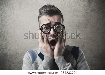 Shocked funny guy staring at camera with head in hands