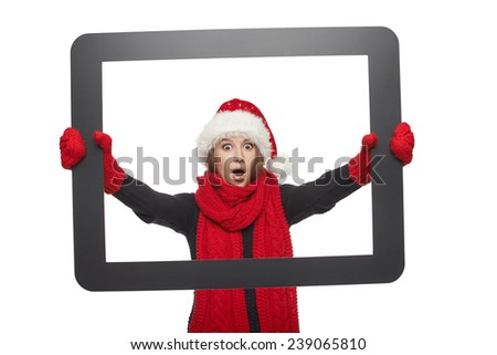 Shocked girl in Santa hat looking through TV computer screen, isolated on white background.  - stock photo