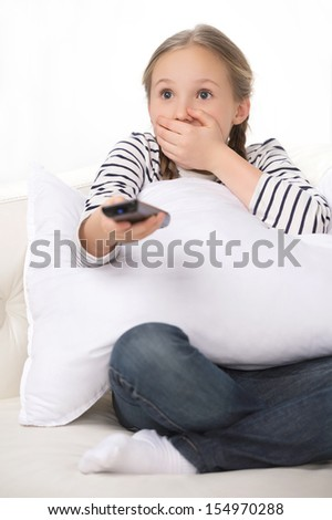 Shocked little girl. Little girl holding remote control and looking scared - stock photo