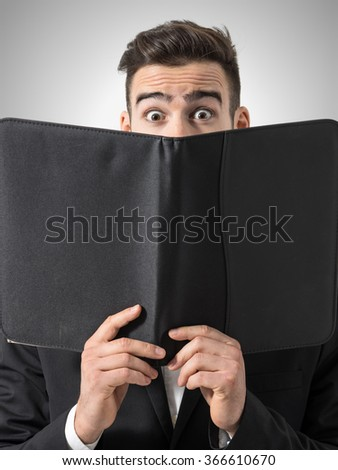 Shocked man expressive eyes reading restaurant menu prices. Portrait over gray studio background.  - stock photo