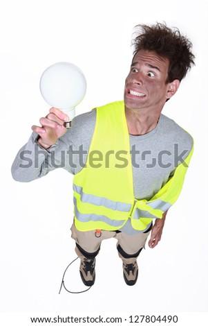 Shocked man holding light-bulb - stock photo
