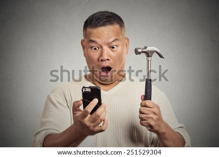 Shocked man looking at his smart phone holding hammer isolated on grey wall background  - stock photo