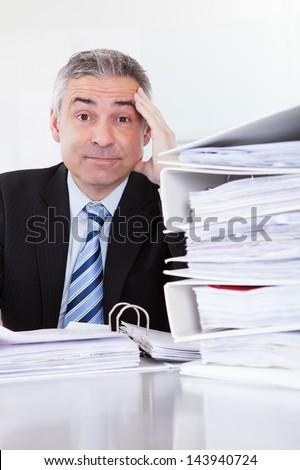 Shocked Mature Businessman Calculating Finance In Office - stock photo