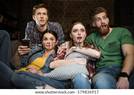 shocked men and women watching movie together at home