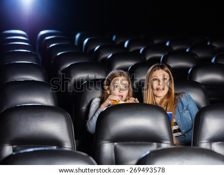 Shocked mother and daughter watching movie in cinema theater - stock photo