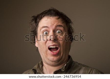 Shocked or surprised expression on a young mans face - stock photo