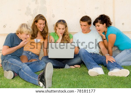 shocked or surprised teens with laptop computer or notebook