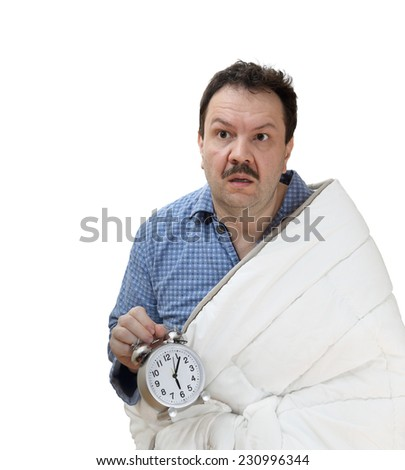 Shocked overslept male in pajamas and blanket holding an alarm clock isolated on white background - stock photo
