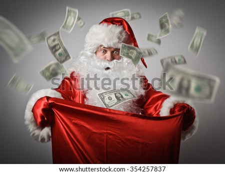 Shocked Santa Claus is looking in to the sack with dollars. Consumerism concept.
