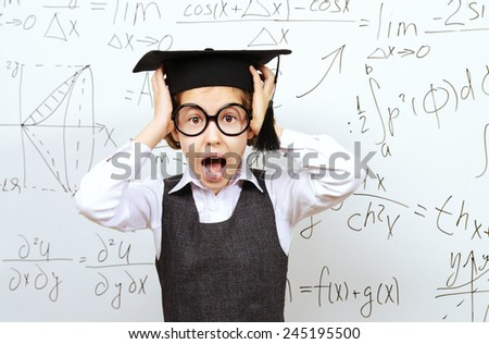 Shocked schoolgirl in big glasses and academic hat stands at the blackboard and holds her head. Educational concept. - stock photo