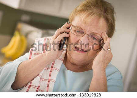 Shocked Senior Adult Woman on Her Cell Phone in Kitchen. - stock photo