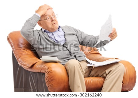Shocked senior gentleman looking at his bills in disbelief seated in an armchair isolated on white background - stock photo