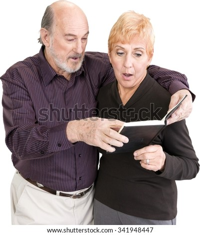 Shocked Senior Male & Female Couple in casual outfit holding book - Isolated