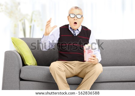 Shocked senior man with popcorn box sitting on a sofa and watching movie at home - stock photo