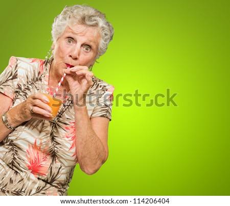 Shocked Senior Woman Drinking Orange Juice Isolated On Green Background - stock photo