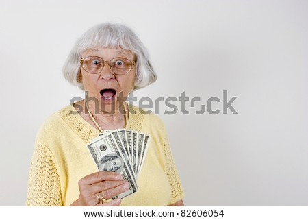 Shocked senior woman holding lots of cash
