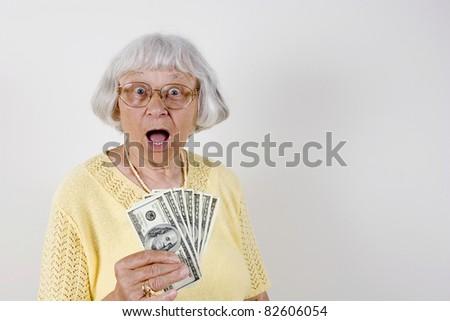 Shocked senior woman holding lots of cash - stock photo