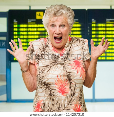 Shocked Senior Woman In Front Of Airport Arrival And Departure Board In Airport - stock photo