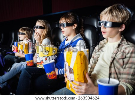 Shocked siblings having snacks while watching 3D movie in cinema theater - stock photo