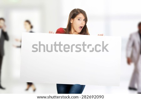 Shocked student woman holding empty banner. - stock photo