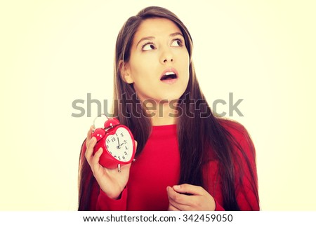 Shocked student woman with alarm clock. - stock photo