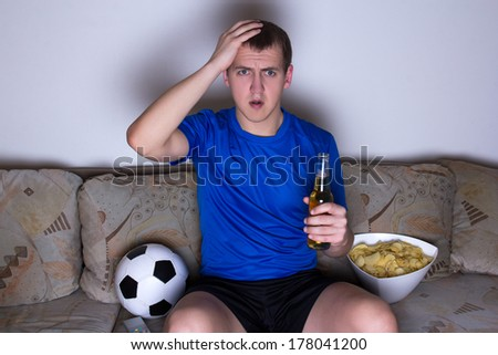shocked supporter in blue uniform sitting on the sofa and watching football with beer and chips - stock photo