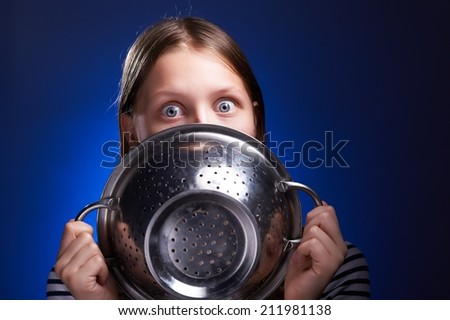 Shocked teen girl hiding her face behind colander - stock photo