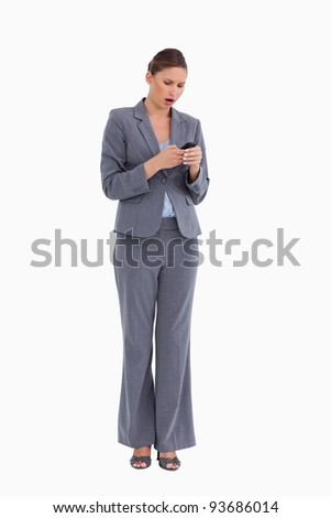 Shocked tradeswoman reading text message against a white background - stock photo