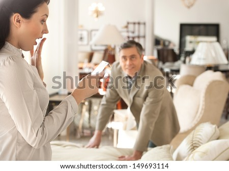 Shocked with a price. Shocked middle-aged woman holding a price while standing near her husband at the furniture store - stock photo