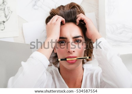 Shocked woman looking at camera with pencil in mouth. Top view on lying artist heard bad news while drawing. Stress, depression, art, workshop , exam concept