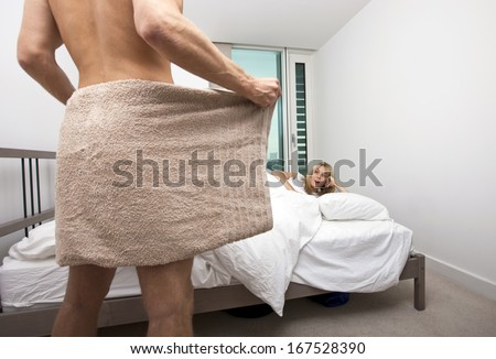 Shocked woman looking at nude man holding towel in bedroom - stock photo