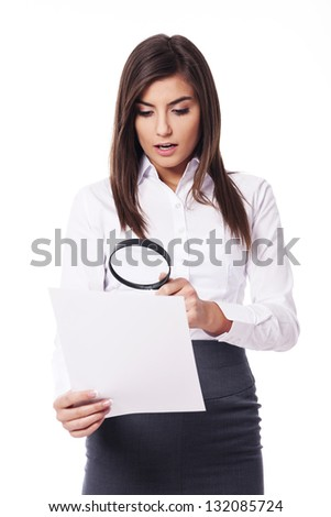 Shocked woman looking through a magnifying glass on documents - stock photo