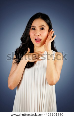 Shocked woman wearing white dress looking at camera and dark blue background with clipping path - stock photo