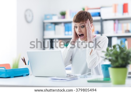 Shocked woman with head in hands having computer problems, she is screaming and staring at the laptop screen - stock photo