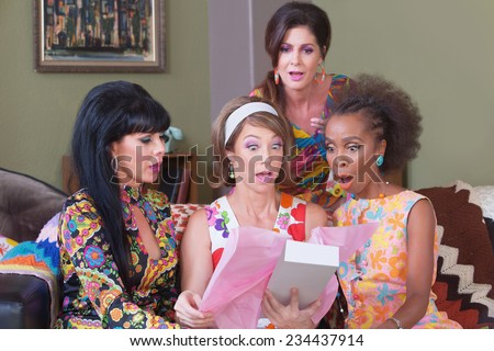 Shocked women looking in box at party - stock photo