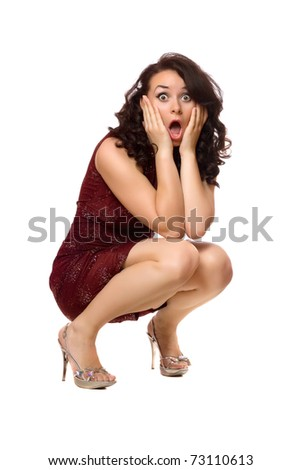 Shocked young brunette in red dress. Isolated