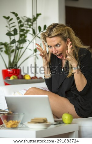 Shocked young business woman blondie looking in her laptop and spreading hands at despair. Expressive nervous woman. Stressed, frustration. - stock photo