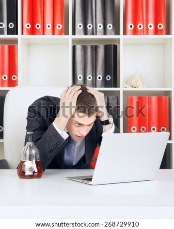 shocked young businessman looking on laptop in his office - stock photo
