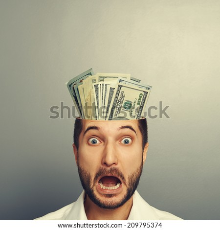 shocked young businessman with money in the head looking at camera and shouting over grey background - stock photo