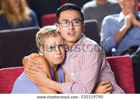 Shocked young couple watching horror in cinema